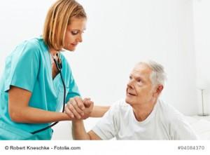 Frau im Pflegeheim hilft einem Senioren beim Aufstehen